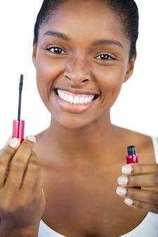 Glimlachende vrouw die haar mascara toont