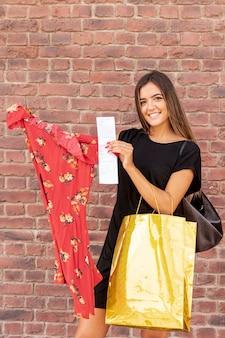 Glimlachende vrouw die haar nieuwe kleding toont