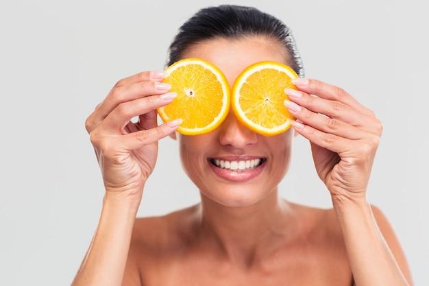 Glimlachende vrouw die haar ogen behandelt met stukjes sinaasappel