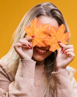 Glimlachende vrouw die haar ogen met esdoornbladeren verbergt tegen gele achtergrond