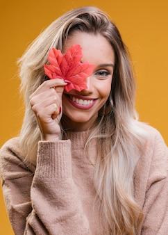 Glimlachende vrouw die haar oog behandelt met rood esdoornblad