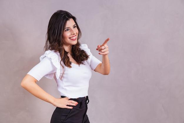 Glimlachende vrouw die haar vinger diagonaal wijst met vrije ruimte voor tekst.