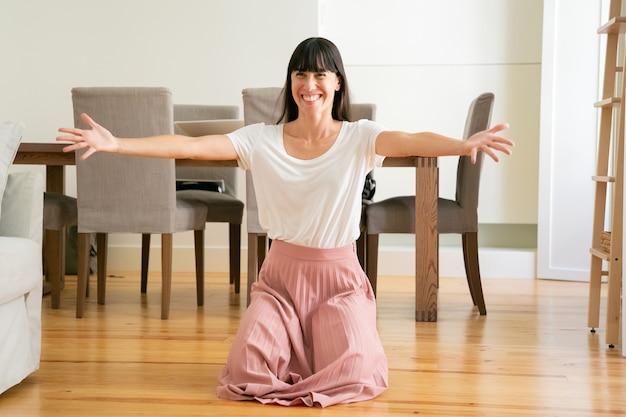 Glimlachende vrouw die handen voor kinderen spreidt en op knieën in de woonkamer staat.