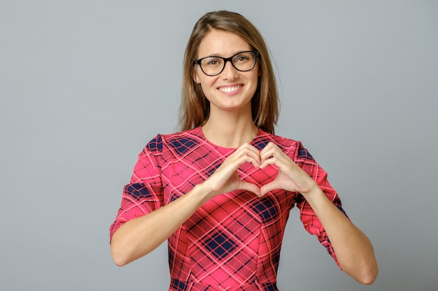 Glimlachende vrouw die hart met twee handen, liefdeteken tonen