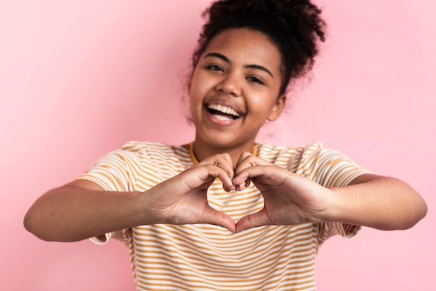 Glimlachende vrouw die hartvorm met handen maakt