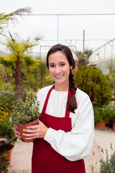 Glimlachende vrouw die het tuinieren kleren draagt en pot in serre houdt
