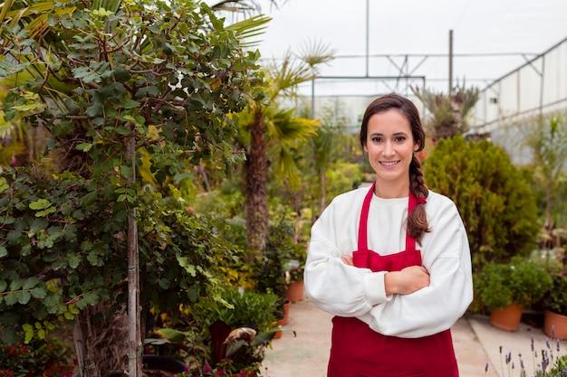 Glimlachende vrouw die het tuinieren kleren in serre draagt