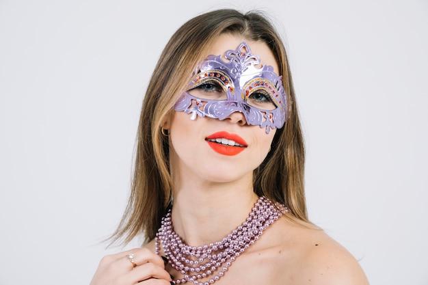Glimlachende vrouw die het venetiaanse masker van maskeradecarnaval dragen