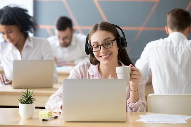 Glimlachende vrouw die hoofdtelefoons draagt die online video tijdens koffiepauze letten