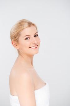 Glimlachende vrouw die huid met huidverzorgingsproducten behandelt