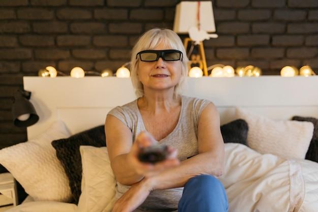 Glimlachende vrouw die in 3d glazen op tv let