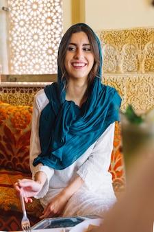 Glimlachende vrouw die in arabisch restaurant eet