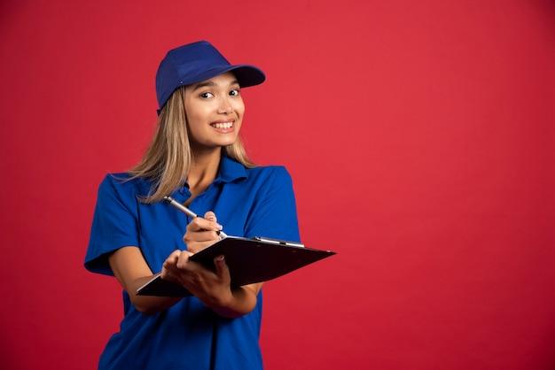 Glimlachende vrouw die in blauw uniform met potlood op klembord schrijft.