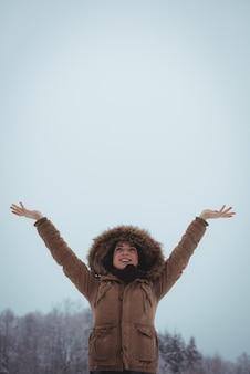 Glimlachende vrouw die in bontjasje van de sneeuwval geniet