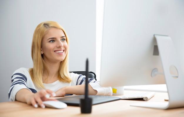 Glimlachende vrouw die in bureau werkt