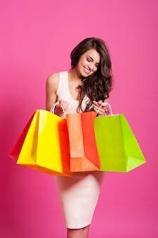 Glimlachende vrouw die in de boodschappentas gluurt