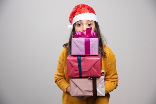 Glimlachende vrouw die in de giftdozen van de kerstmanhoed houdt.