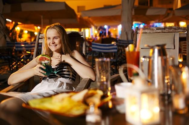 Glimlachende vrouw die in een cafetaria drinkt