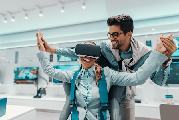 Glimlachende vrouw die in formele slijtage virtual reality-technologie uitproberen terwijl het zitten als voorzitter in technologie-opslag