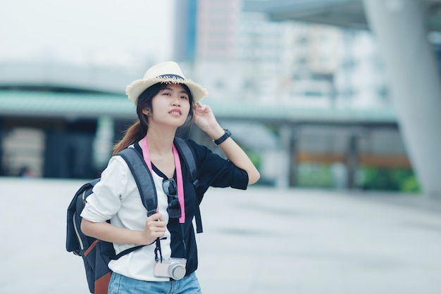 Glimlachende vrouw die in openlucht, jonge dame het bewonderen stadsgezicht lopen met gang en gebouwen op achtergrond lopen.