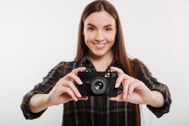Glimlachende vrouw die in overhemd retro camera houdt