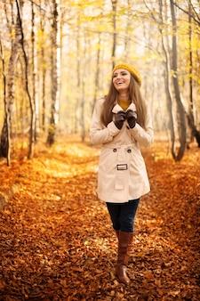 Glimlachende vrouw die in park bij de herfstseizoen loopt
