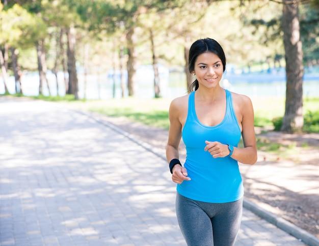 Glimlachende vrouw die in park loopt