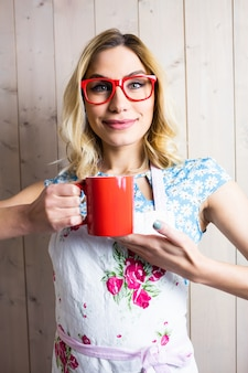 Glimlachende vrouw die in schort een koffiemok houdt