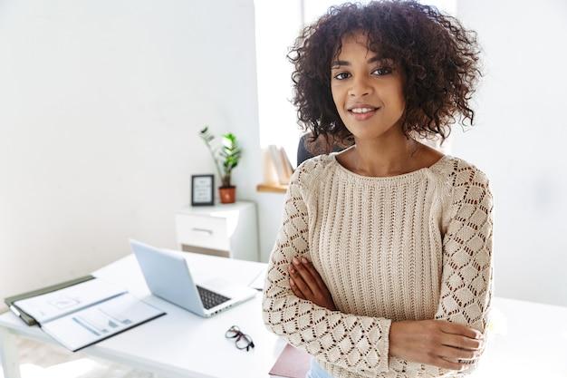 Glimlachende vrouw die in vrijetijdskleding naar de camera kijkt met gekruiste armen terwijl ze bij de tafel op kantoor staat