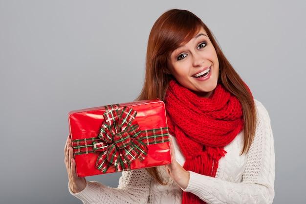 Glimlachende vrouw die in warme kleren de gift van kerstmis houdt
