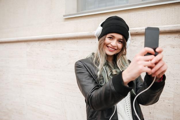 Glimlachende vrouw die in warme kleren foto op de straat maakt