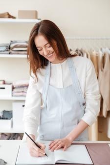 Glimlachende vrouw die in workshop ontwerpt