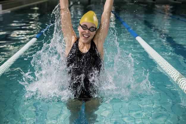 Glimlachende vrouw die in zwempak in de pool springt