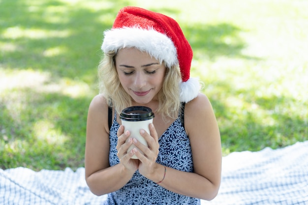 Glimlachende vrouw die kerstmanhoed draagt en van koffie in park geniet