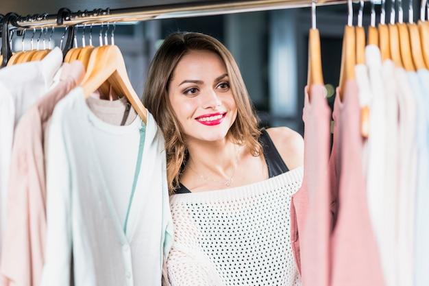 Glimlachende vrouw die kleren bekijken die op hark in opslag hangen