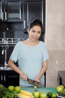 Glimlachende vrouw die komkommer in de keuken snijdt