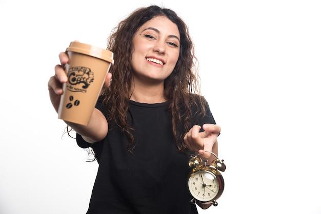 Glimlachende vrouw die kopje koffie met klok op witte achtergrond toont. hoge kwaliteit foto