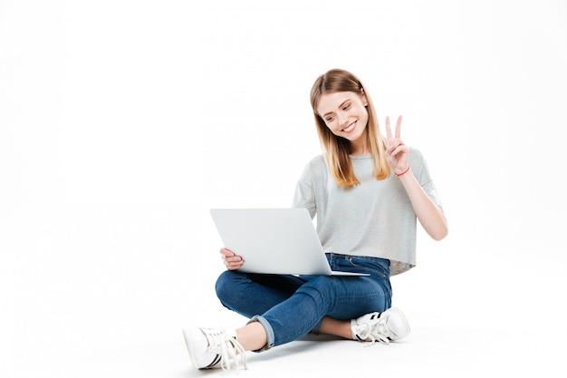 Glimlachende vrouw die laptop computer met behulp van