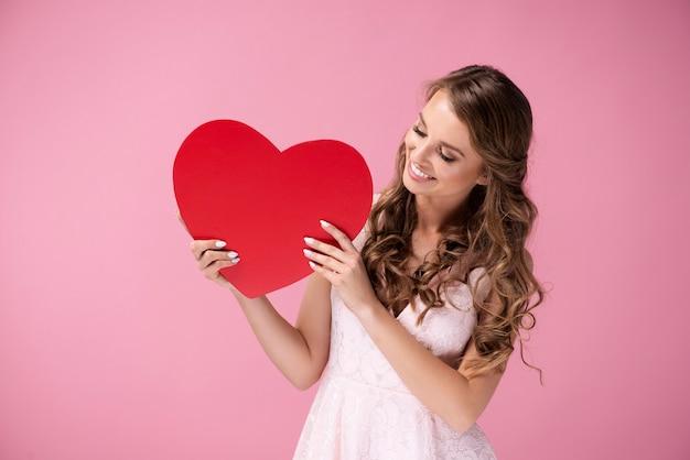 Glimlachende vrouw die lege valentijnskaartkaart bekijkt