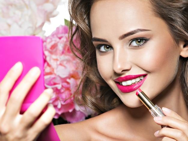 Glimlachende vrouw die lippenstift toepast. mooi meisje maakt make-up