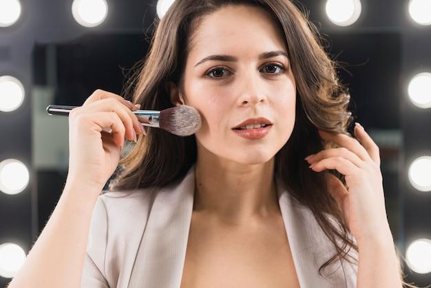 Glimlachende vrouw die make-up op spiegelachtergrond toepast