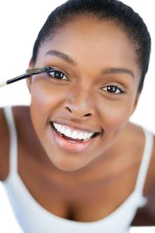 Glimlachende vrouw die mascara op haar wimper zet