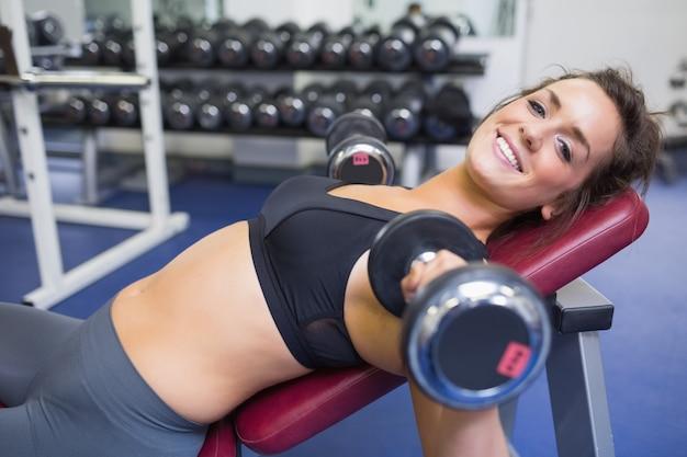 Glimlachende vrouw die met gewichten opleiden
