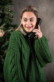 Glimlachende vrouw die met groene sweater een gesprek met de mobiele telefoon houdt