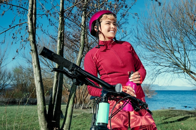 Glimlachende vrouw die met haar fiets in het bos dichtbij een meer rust na een training