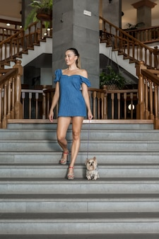 Glimlachende vrouw die met hond onderaan stappen lopen