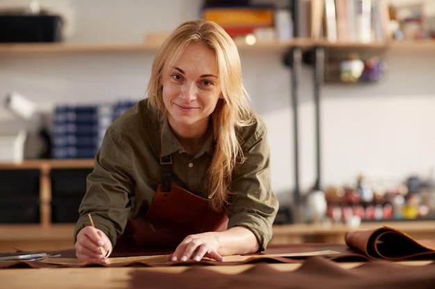 Glimlachende vrouw die met leer werkt