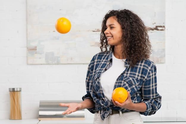 Glimlachende vrouw die met sinaasappelen jongleren