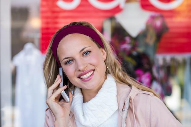 Glimlachende vrouw die met smartphone telefoneert