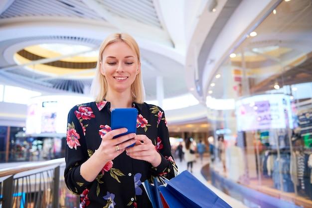 Glimlachende vrouw die mobiele telefoon in winkelcentrum gebruikt shopping